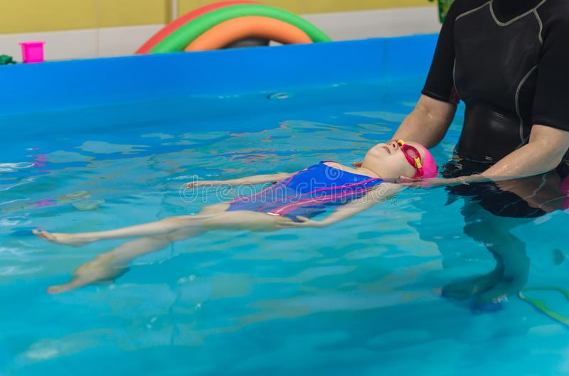 A little girl of European appearance in a pink rubber cap learning to swim in the pool.  stock photo