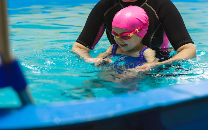 A little girl of European appearance in a pink rubber cap learning to swim in the pool stock images