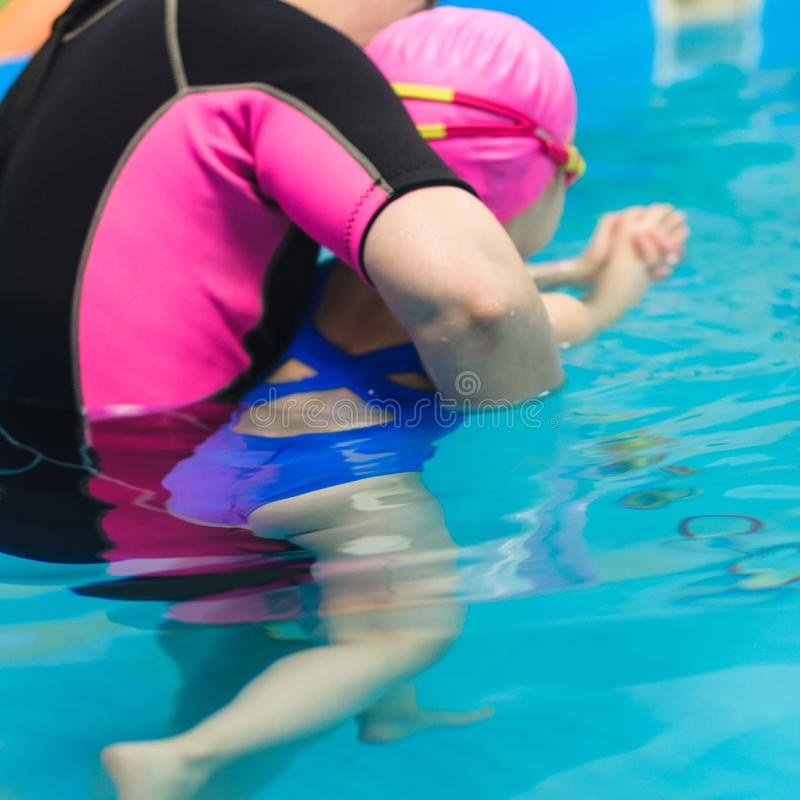 A little girl of European appearance in a pink rubber cap learning to swim in the pool.  stock images