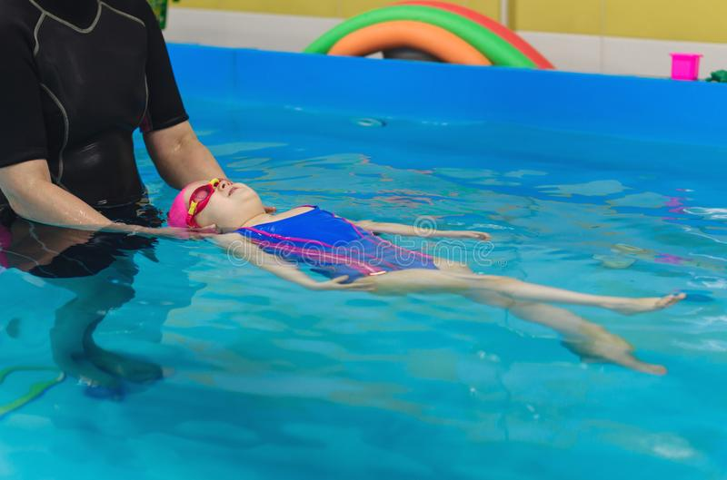 A little girl of European appearance in a pink rubber cap learning to swim in the pool stock photography