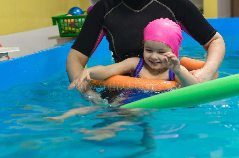 A little girl of European appearance in a pink rubber cap learning to swim in the pool.  royalty free stock photo