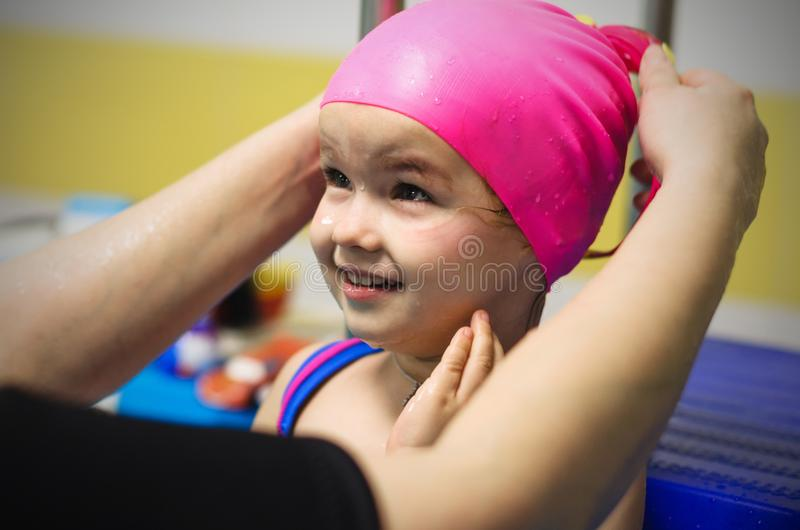 A little girl of European appearance, wearing a pink rubber swimming cap in the pool.  royalty free stock photo
