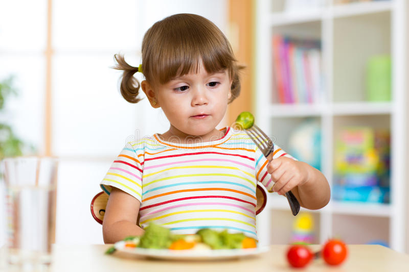Little girl examines Brussels sprouts. Child with healthy food sitting at table in nursery. Little cute girl examines Brussels sprouts. Child with healthy food royalty free stock photo