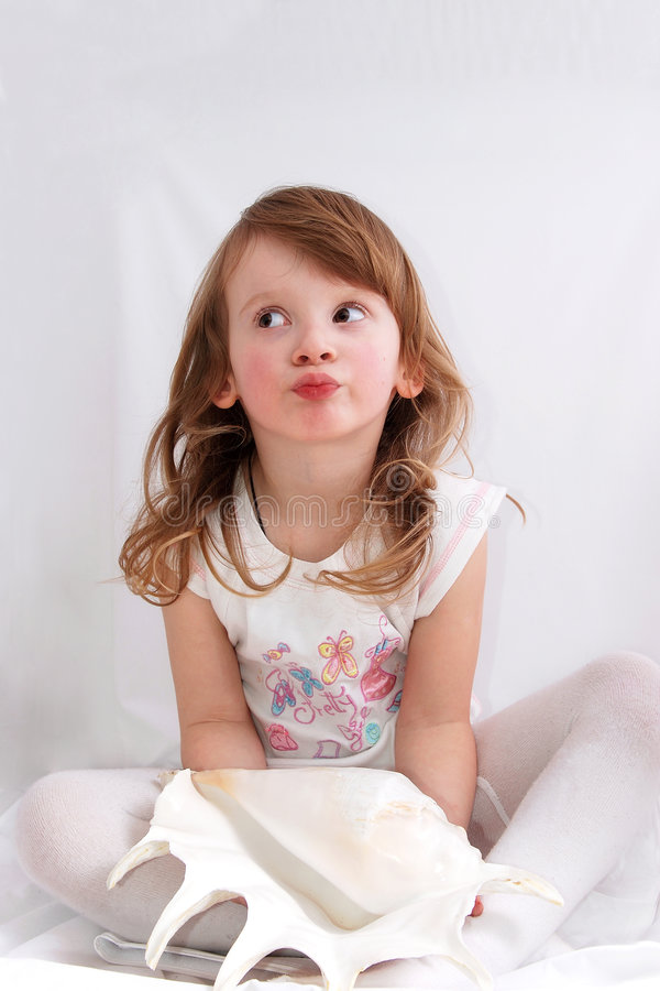 Little girl with an exotic seashell royalty free stock images
