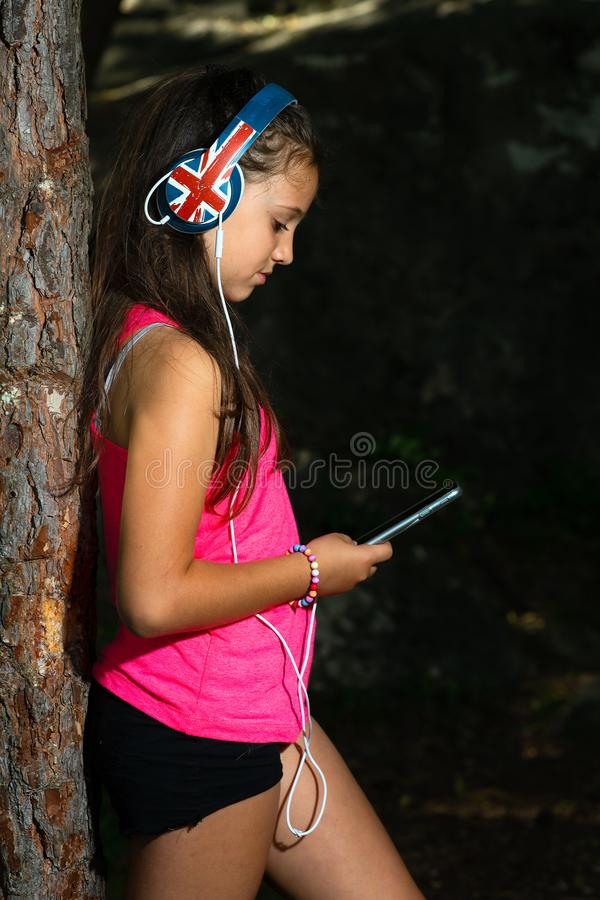 Little girl explores social networks with her smartphone while l royalty free stock image