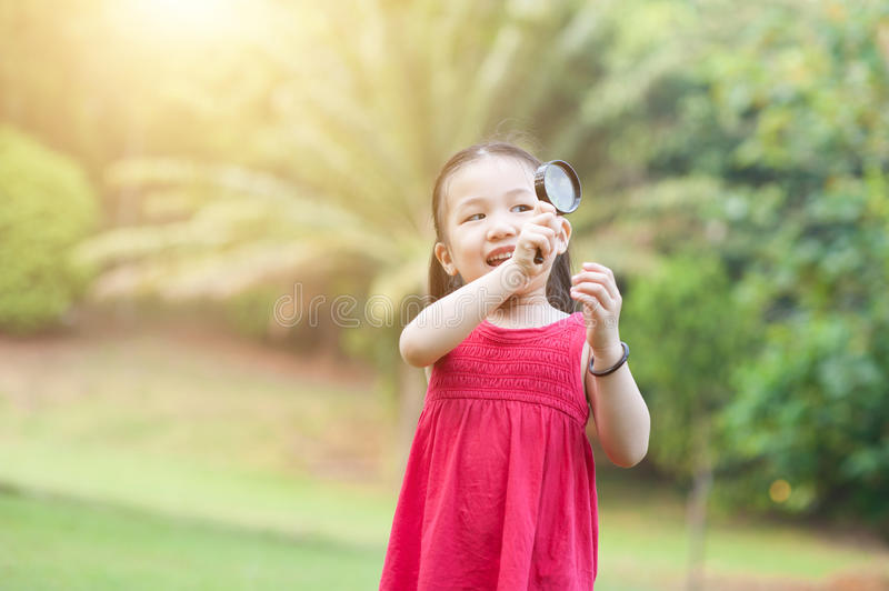 Little girl exploring nature with magnifier glass at outdoors. stock photography