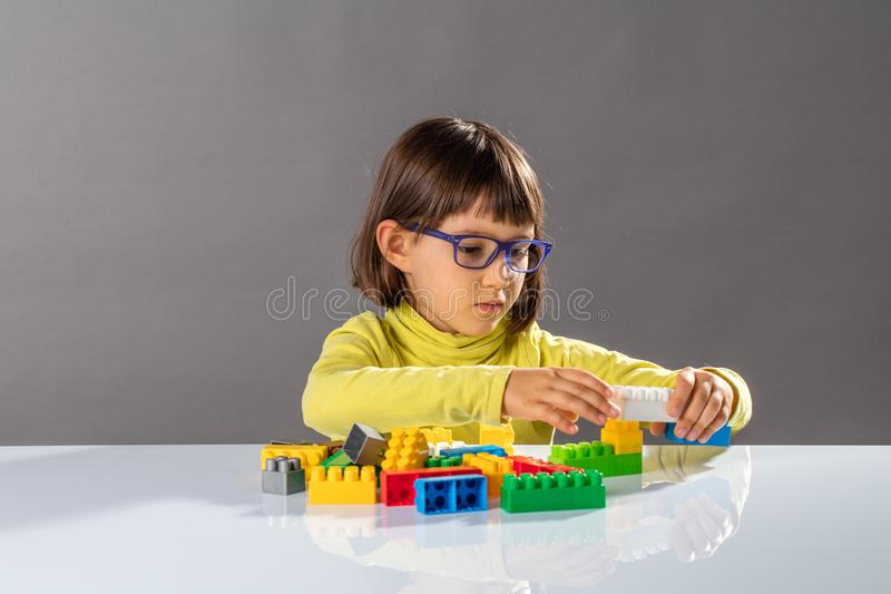 Little girl playing, thinking about organizing toys with design stock images