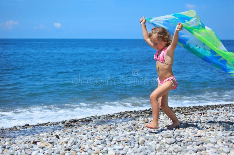 Little girl with fabric on stony seacoast stock photos