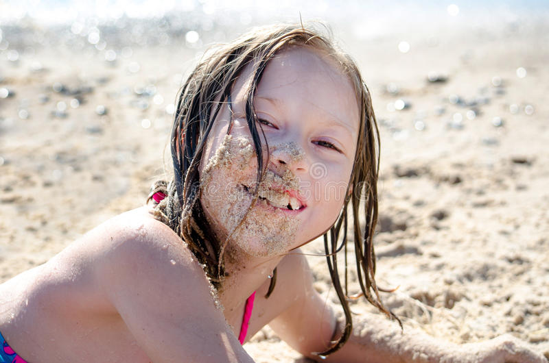 Little girl with face full of sand royalty free stock image