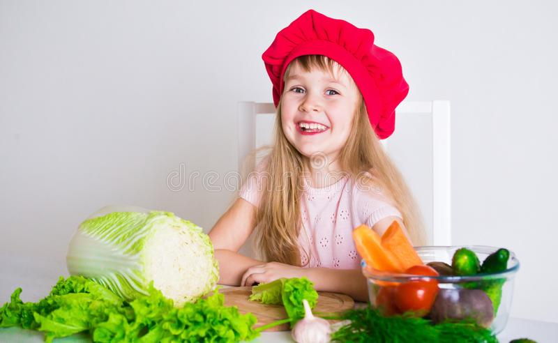 Little girl face, red hat, close up. Beautiful little girl, has happy fun smiling face, big pretty eyes, long blonde hair, red hat. Cooks in kitchen appetizing royalty free stock images