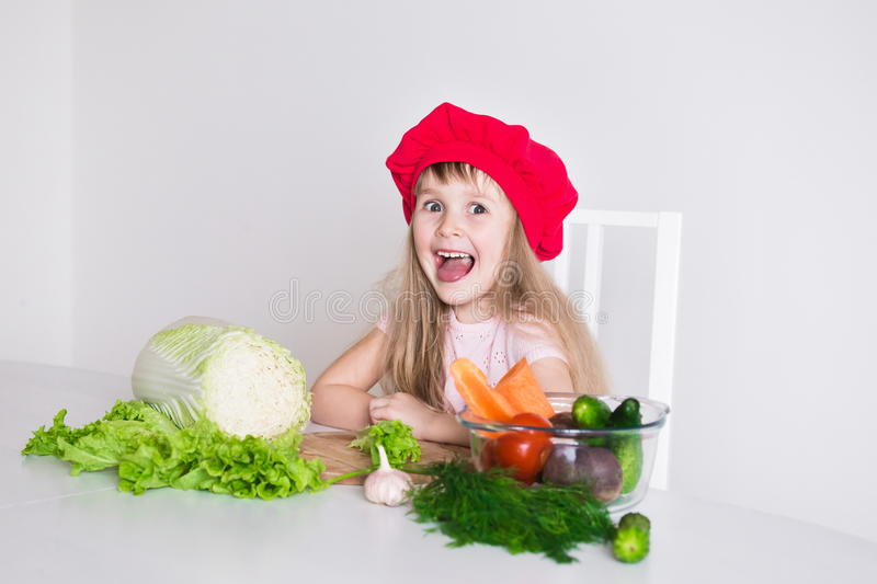 Little girl face, red hat, close up. Beautiful little girl, has happy fun smiling face, big pretty eyes, long blonde hair, red hat. Cooks in kitchen appetizing royalty free stock photography