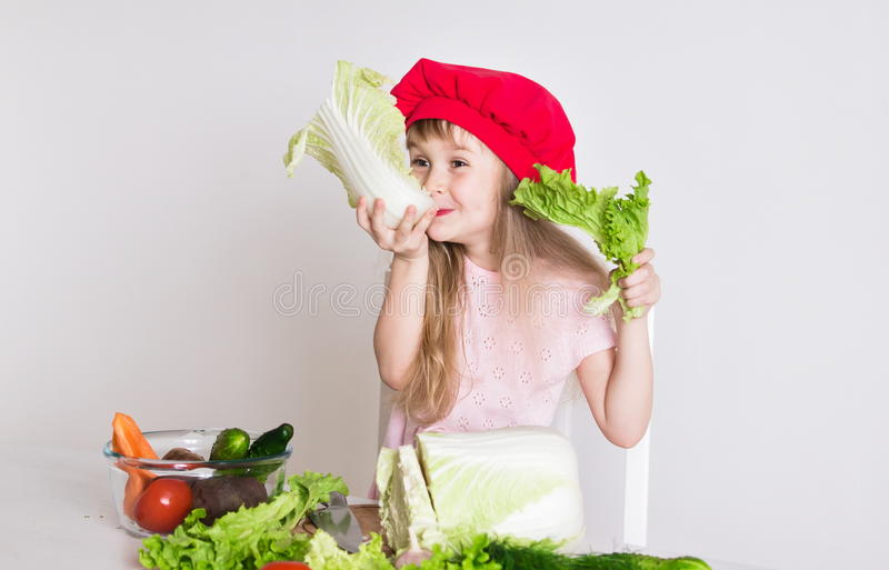 Little girl face, red hat, close up. Beautiful little girl, has happy fun smiling face, big pretty eyes, long blonde hair, red hat. Cooks in kitchen appetizing stock image