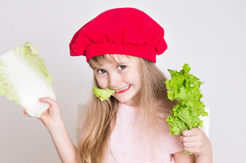 Little girl face, red hat, close up. Beautiful little girl, has happy fun smiling face, big pretty eyes, long blonde hair, red hat. Cooks in kitchen appetizing stock photography