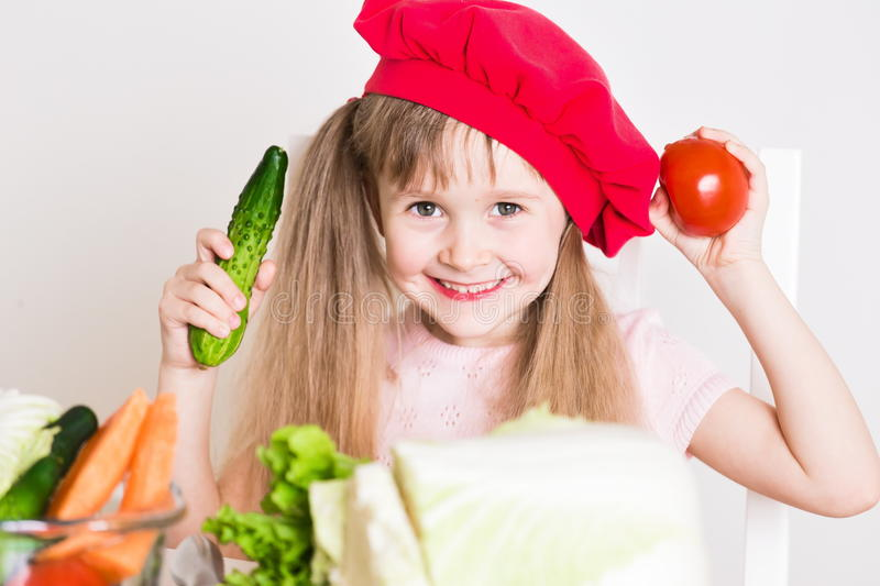 Little girl face, red hat, close up. Beautiful little girl, has happy fun smiling face, big pretty eyes, long blonde hair, red hat. Cooks in kitchen appetizing royalty free stock image