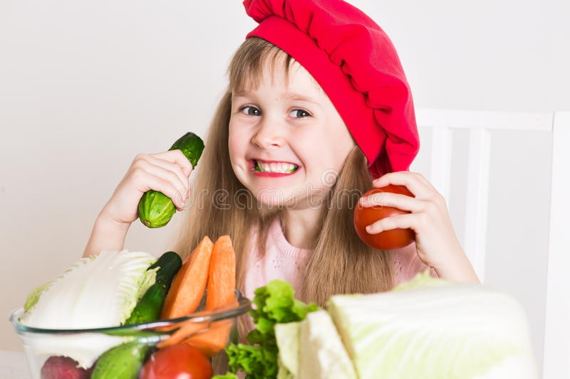 Little girl face, red hat, close up. Beautiful little girl, has happy fun smiling face, big pretty eyes, long blonde hair, red hat. Cooks in kitchen appetizing stock photo