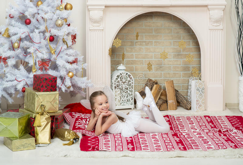 Little girl in fairy pixi costume dress is posing beside the Christmas tree. Little girl in fairy pixi costume dress poses beside the Christmas tree . X-mass and stock photography