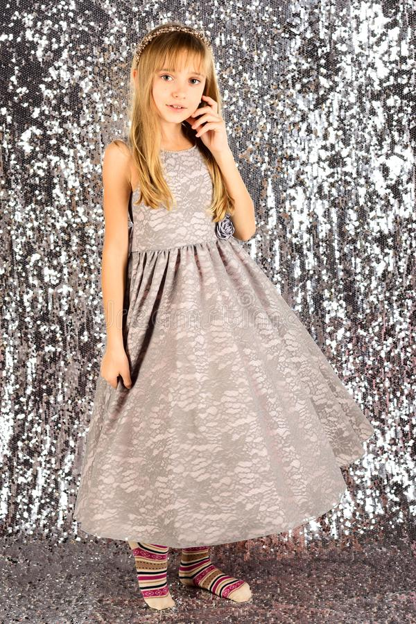 Little girl in fashionable dress, prom. Child girl in stylish glamour dress, elegance. Fashion model on silver. Background, beauty. Look, hairdresser, makeup stock photos