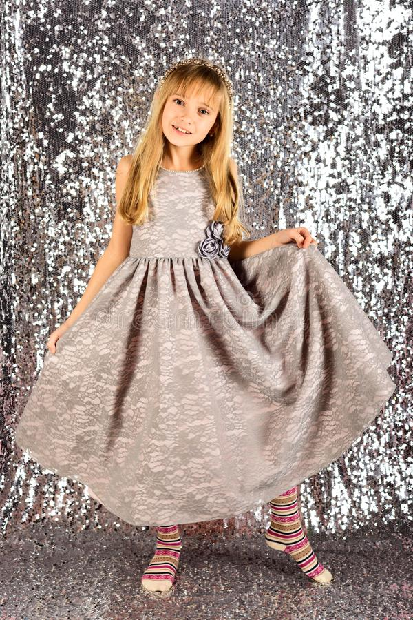 Little girl in fashionable dress, prom. Fashion model on silver background, beauty. Look, hairdresser, makeup. Child. Girl in stylish glamour dress, elegance royalty free stock photo