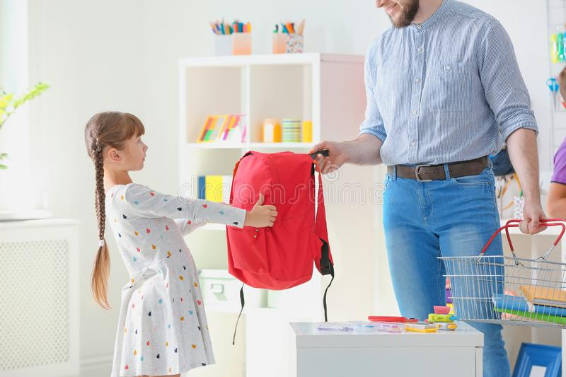 Little girl with father choosing school stationery stock image