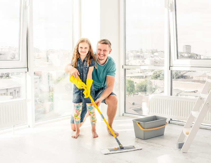 Little girl with father cleaning the floor royalty free stock photo