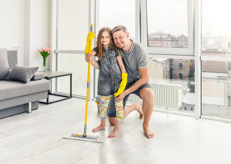 Little girl with father cleaning the floor stock photos