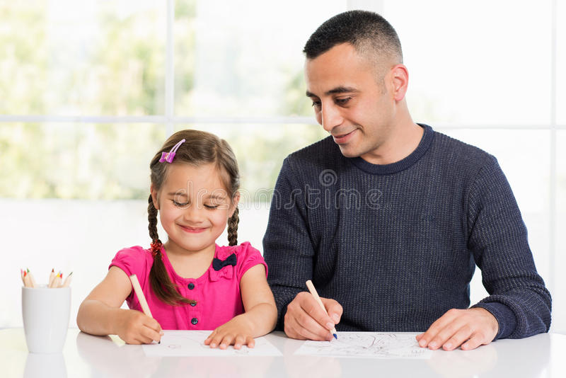 Little Girl And Father Drawing Pictures Together royalty free stock photography