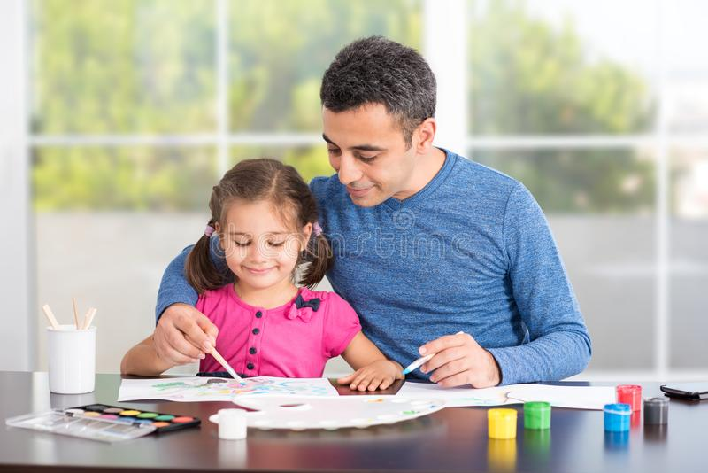 Little Girl And Father Drawing Pictures Together stock images