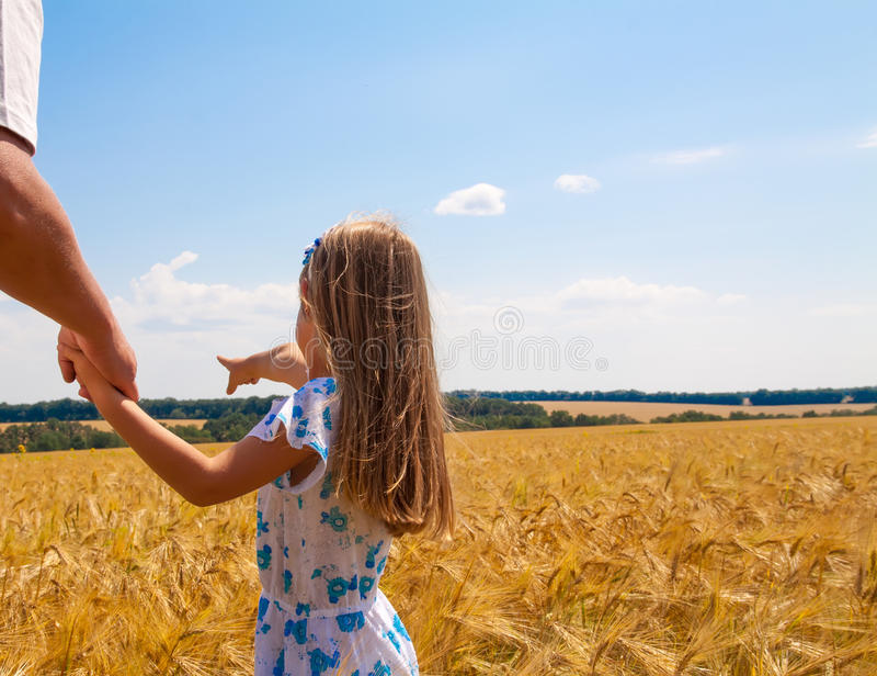 Little girl and father on the field. Little girl holding his father's hand on the field royalty free stock photo