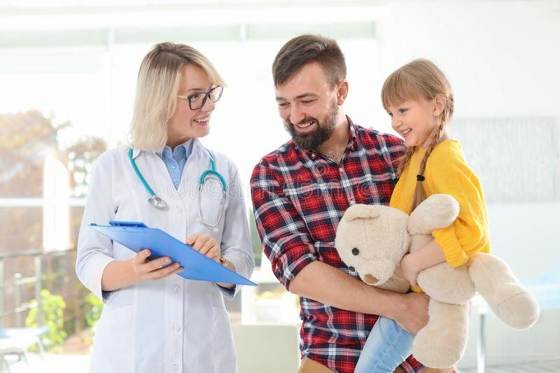 Little girl with father visiting children`s doctor stock photo