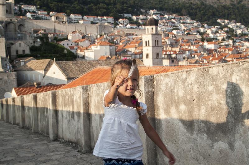 Little girl with feather on the walls enclosing the old town of Dubrovnik at sunset. Croatia, view, red, europe, ancient, famous, blue, mediterranean, sky royalty free stock photography