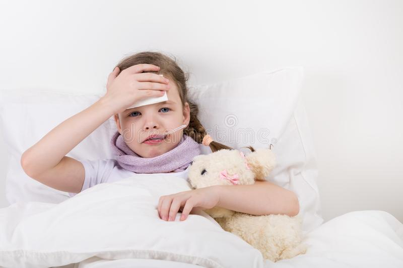 The little girl fell ill, her fever rose, she holds her hand to the sick head. Hugs the toy dog stock photography