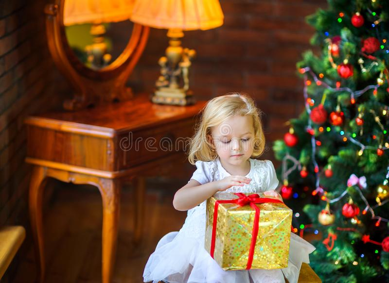 Little girl in a festive dress opens a gift. Beautiful little girl in a festive dress opens a gift sitting near a Christmas tree royalty free stock images