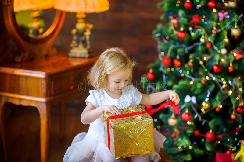 Little girl in a festive dress opens a gift. Beautiful little girl in a festive dress opens a gift sitting near a Christmas tree stock photo