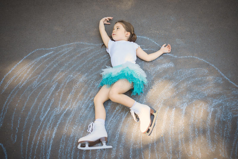 Little girl figure skating at imaginary skating rink arena. Laying down on asphalt after drawing rink arena with chalk, dreaming of becoming professional ice royalty free stock photo