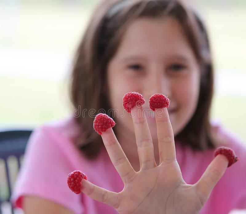 Little girl with five raspberries royalty free stock photography