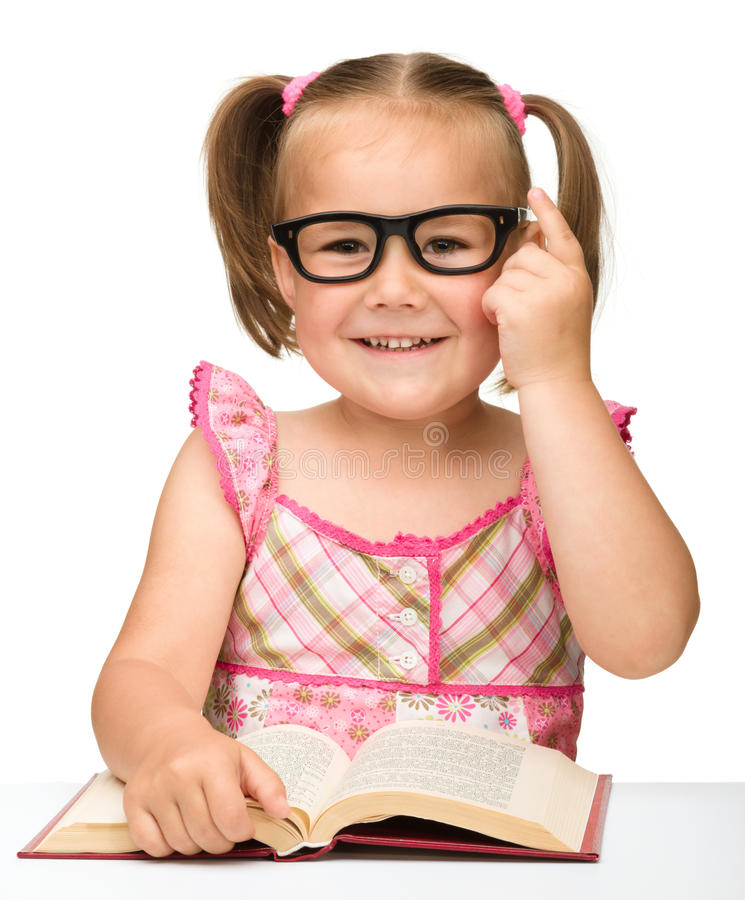 Little girl is flipping over pages of a book. Cute little girl wearing glasses is flipping over pages of a book, isolated on white royalty free stock photos