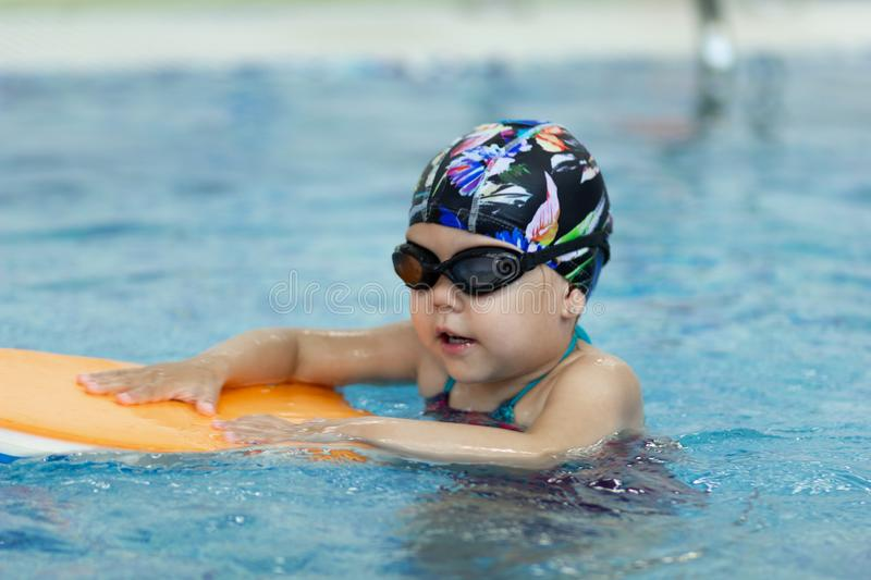 Little girl with float board in the swimming pool stock image