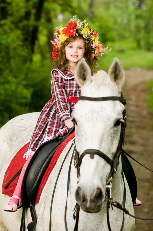 Little girl in floral wreath riding horse. In the forest royalty free stock images