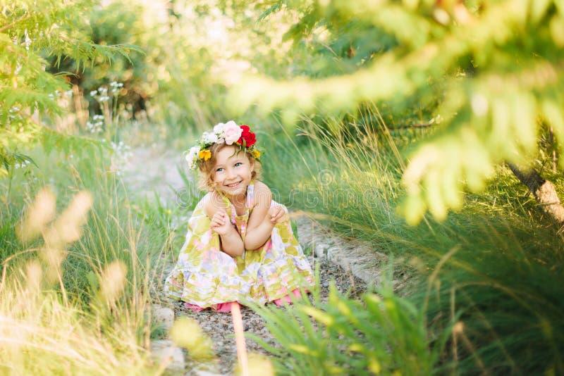 Little girl in flower wreath in the garden. In summer royalty free stock photos