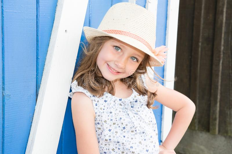 little girl in flowers dress and hat relaxing on the beach near wood hut summer vacation and travel concept stock photo