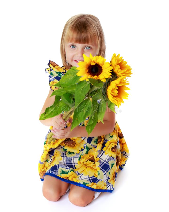 Little girl with flowers of sunflower. royalty free stock photography