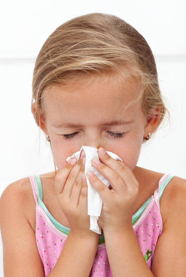Little girl with the flu blowing nose stock photos