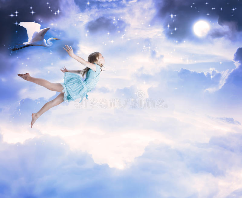Little girl flying into the blue night sky royalty free stock photography