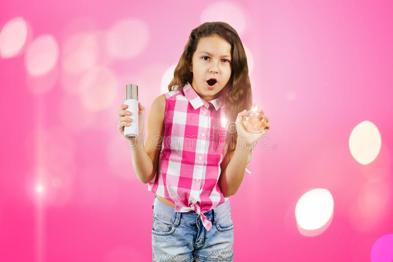 Little girl in the form of a glamorous diva with scented water a. Nd hairspray on a pink background with a bokeh royalty free stock photo