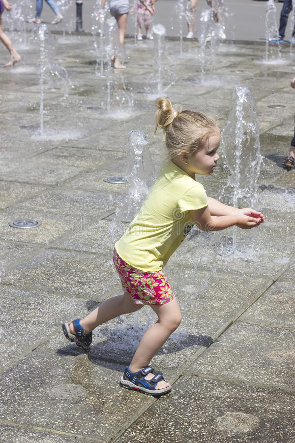 Little girl at the fountains. Little girl playing at the fun fountains stock photo