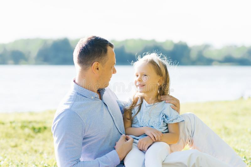 A little girl four or five years old sits on dad`s lap against the lake in the summer, they look at each other stock image