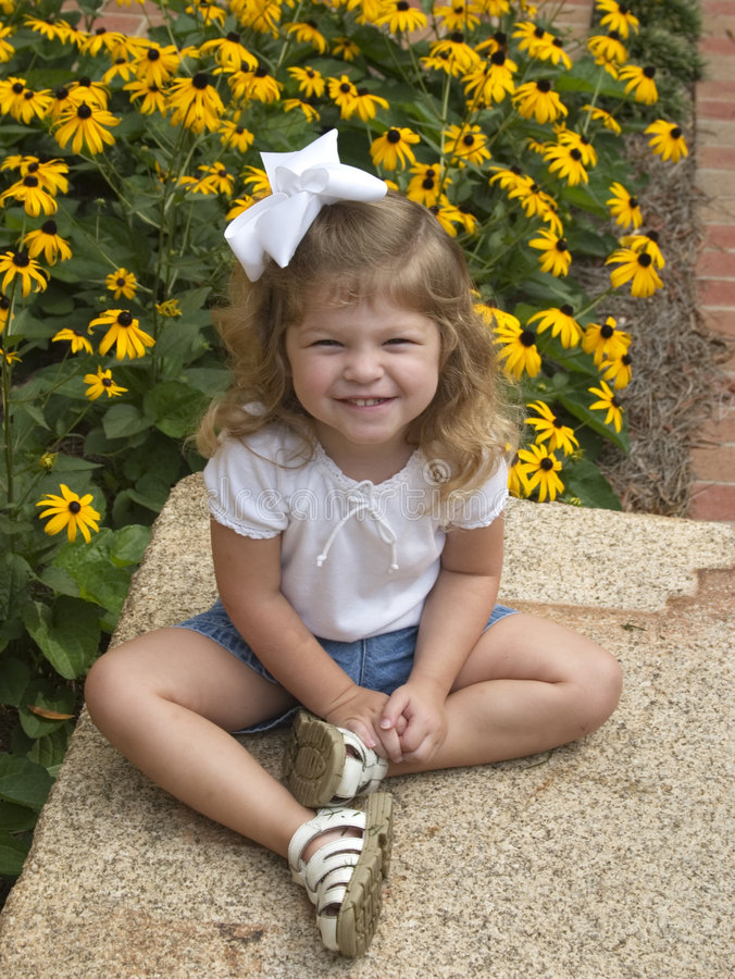Little girl in front of flowers royalty free stock image