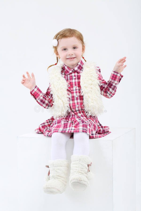 Little girl in fur boots and vest sits on big cube