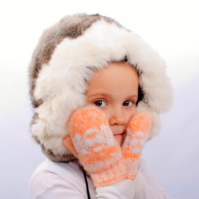 The little girl in a fur cap. And mittens on a white background royalty free stock photography