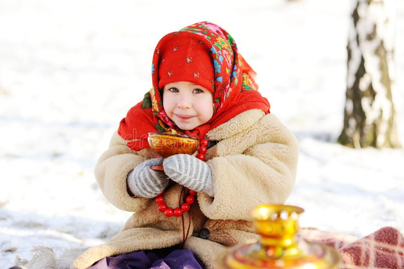 Little girl in a fur coat and red scarf Russian drinking tea on royalty free stock image
